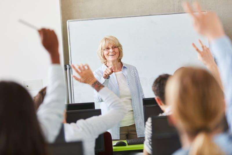 Mãos levantadas em lições da escola imagens de stock