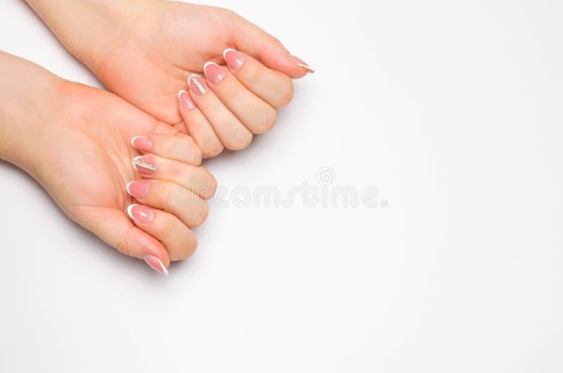 Mãos macias fêmeas com tratamento de mãos francês bonito Fundo branco isolado Pregos longos Lugar para o texto Copie o espaço imagem de stock royalty free
