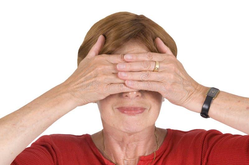 Mãos maduras da mulher nos olhos fotografia de stock