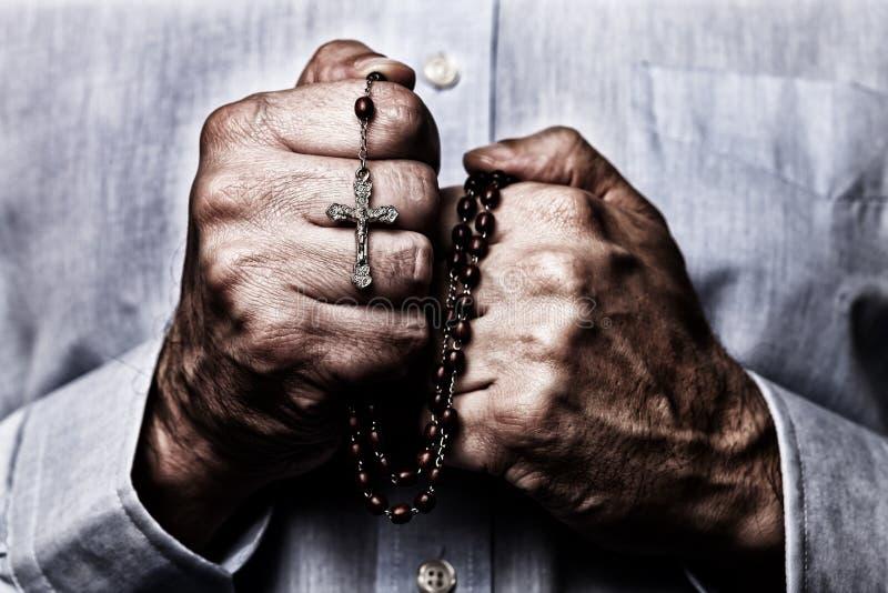 Mãos masculinas afro-americanos que rezam guardando um rosário dos grânulos com Jesus Christ na cruz ou no crucifixo imagens de stock royalty free