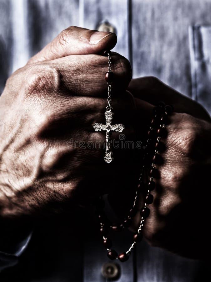 Mãos masculinas afro-americanos que rezam guardando um rosário dos grânulos com Jesus Christ na cruz ou no crucifixo no fundo pre imagens de stock