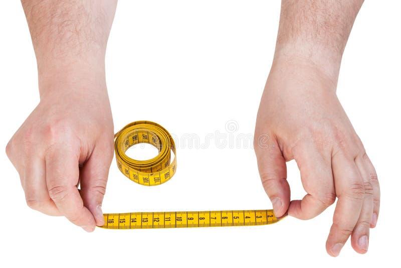 Mãos masculinas com a fita de medição do alfaiate isolada fotografia de stock