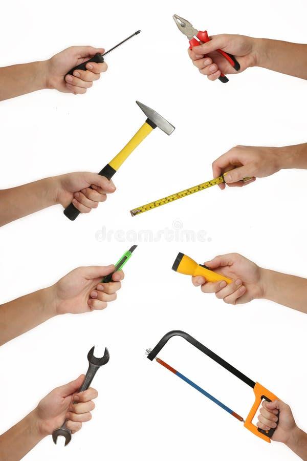 Mãos masculinas com lotes das ferramentas da melhoria da casa isoladas no branco imagem de stock royalty free
