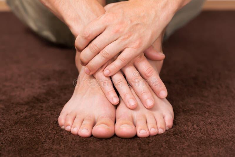 Mãos masculinas cruzadas sobre os pés de descanso fotografia de stock