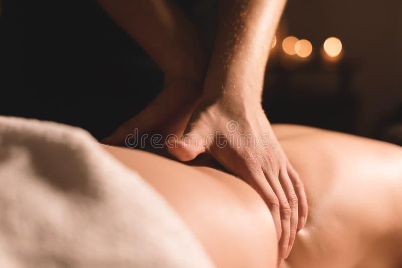 Mãos masculinas do close-up que fazem a massagem cura com óleo a uma moça em um escritório escuro da cosmetologia Chave escura imagem de stock royalty free