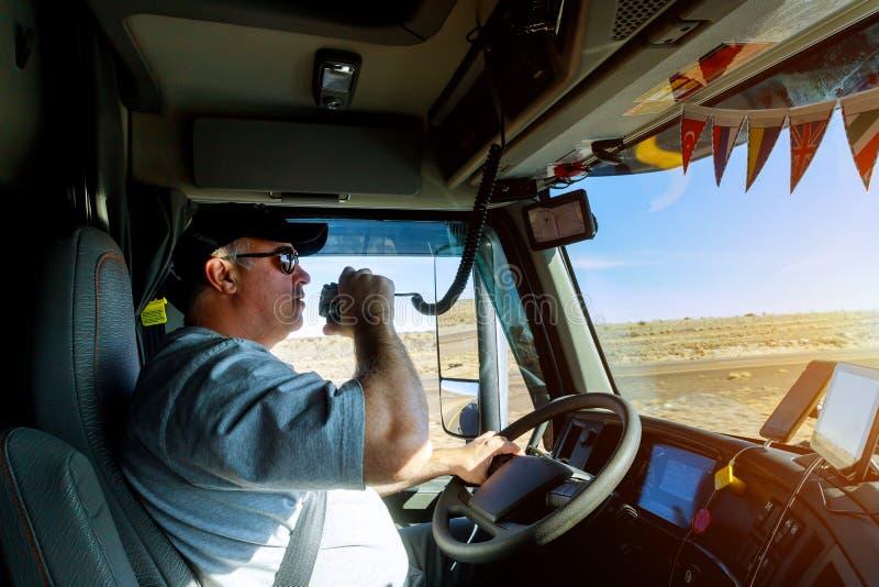 Mãos masculinas do motorista que guardam o rádio e o volante foto de stock