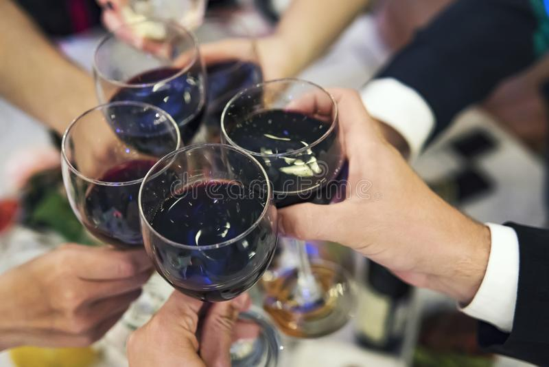 Mãos masculinas e fêmeas com vidros enchidos do vinho tinto acima do tabletop do restaurante Brindes e secadoras de roupa bebendo imagem de stock royalty free