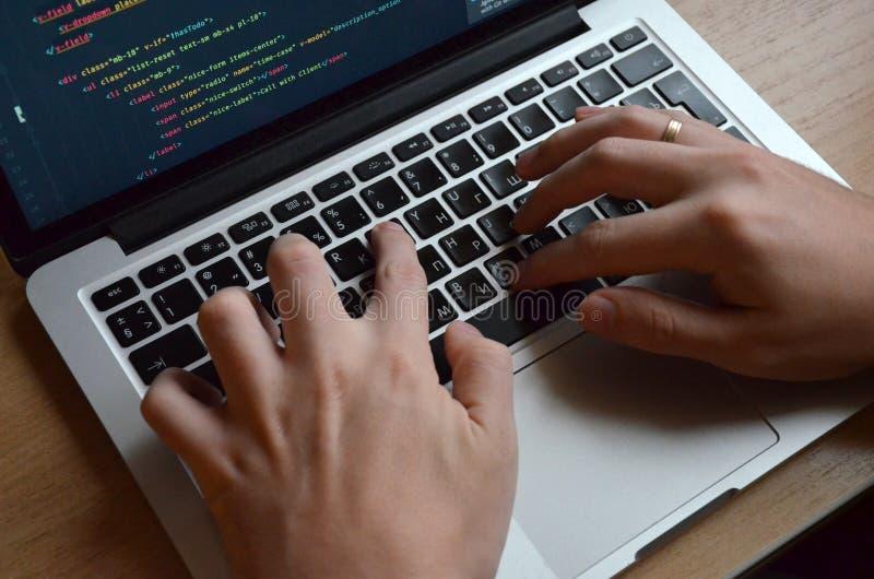 Mãos masculinas em um teclado preto Codificação europeia em um computador S foto de stock royalty free