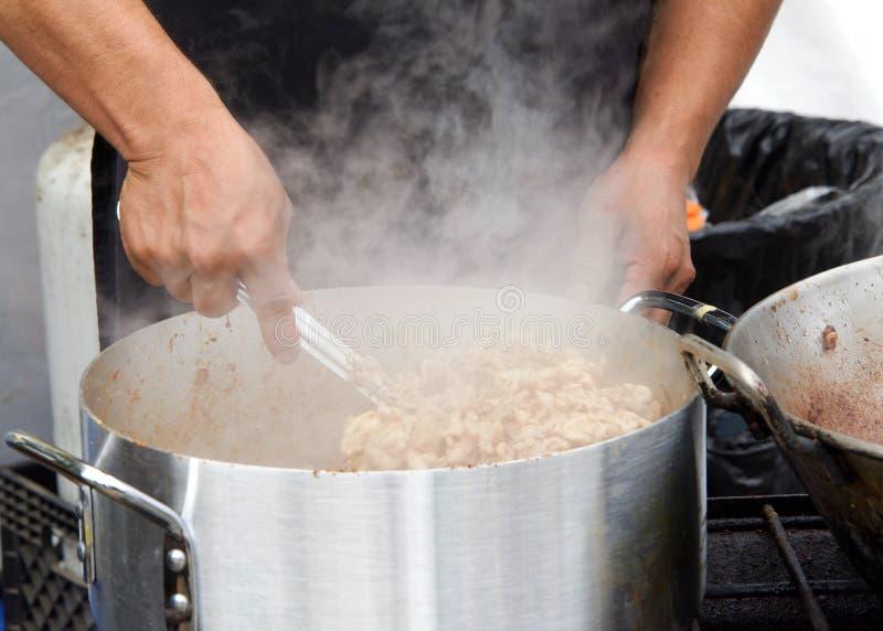 Mãos masculinas que agitam cozinhando pedaços quentes da galinha fotografia de stock royalty free
