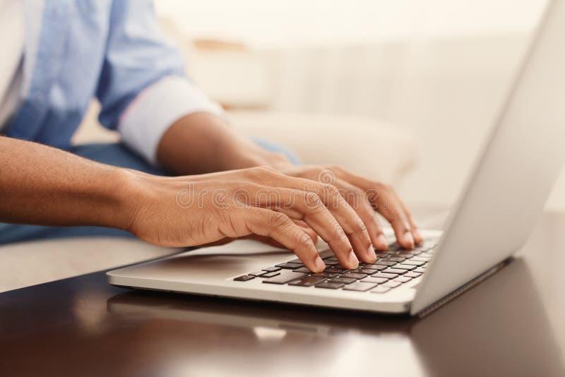 Mãos masculinas que datilografam o texto ou que programam o código no portátil foto de stock