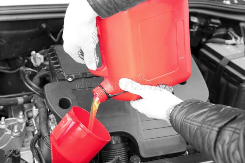 Mãos masculinas que derramam o óleo de motor do cartucho fotografia de stock