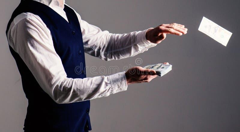 Mãos masculinas que desperdiçam o dinheiro, dinheiro, dólares Mãos masculinas no dinheiro de jogo do vestuário formal no fundo ci fotos de stock royalty free