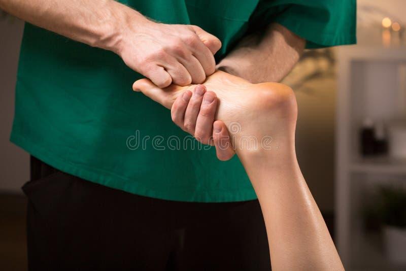 Mãos masculinas que fazem a massagem do pé imagem de stock royalty free