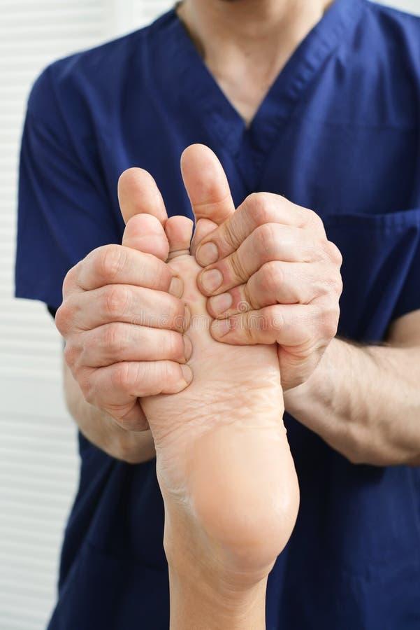 Mãos masculinas que fazem a massagem do pé foto de stock royalty free