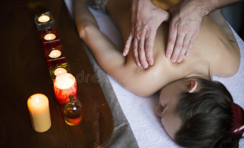 Mãos masculinas que fazem massagens a parte traseira fêmea Velas no fundo Cuidados médicos e para relaxar o conceito fotos de stock