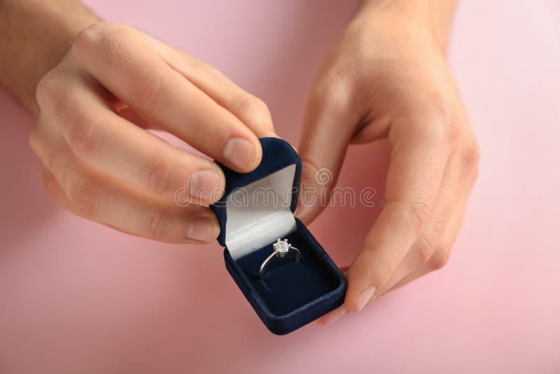 Mãos masculinas que guardam a caixa com anel de noivado no fundo da cor fotografia de stock royalty free