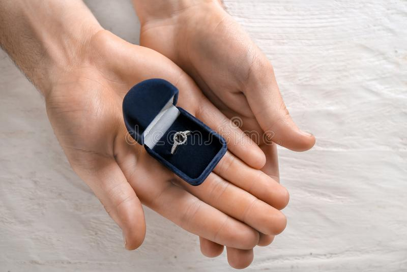 Mãos masculinas que guardam a caixa com anel de noivado no fundo de madeira claro fotos de stock royalty free