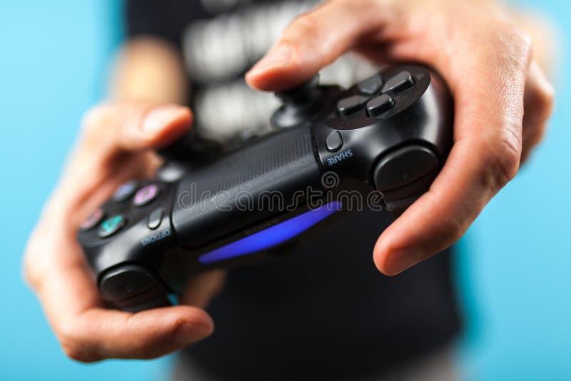 Mãos masculinas que guardam um controlador PS4 fotos de stock