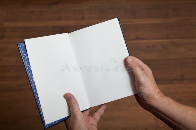 Mãos masculinas que guardam um livro aberto foto de stock royalty free