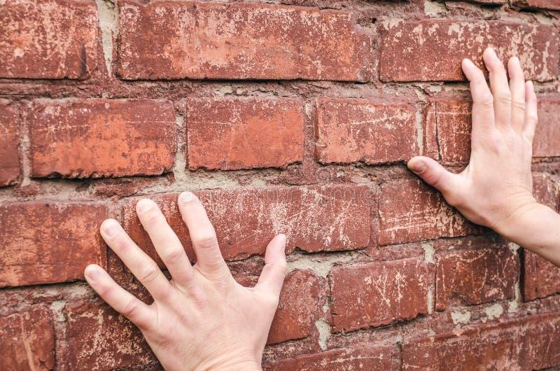 Mãos masculinas que guardam uma parede de tijolo Deadend fotografia de stock