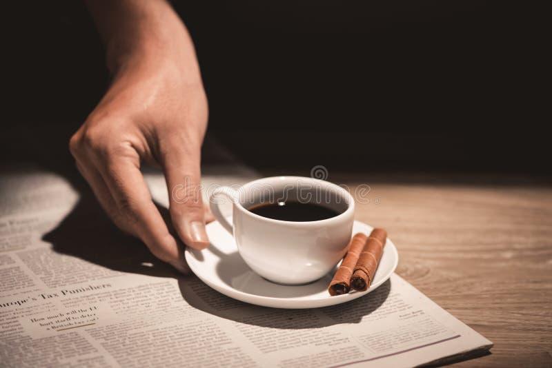 Mãos masculinas que guardam uma xícara de café sobre a tabela de madeira fotografia de stock royalty free