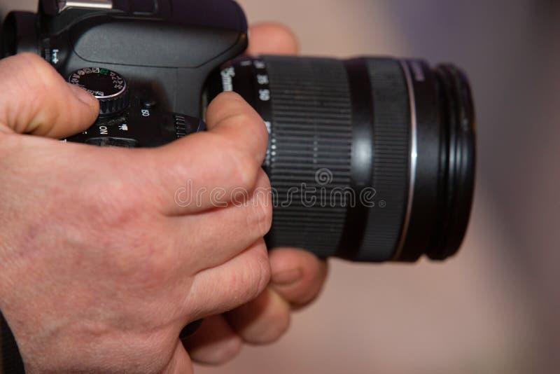 Mãos masculinas que mantêm um fim digital da câmera de SLR imagens de stock