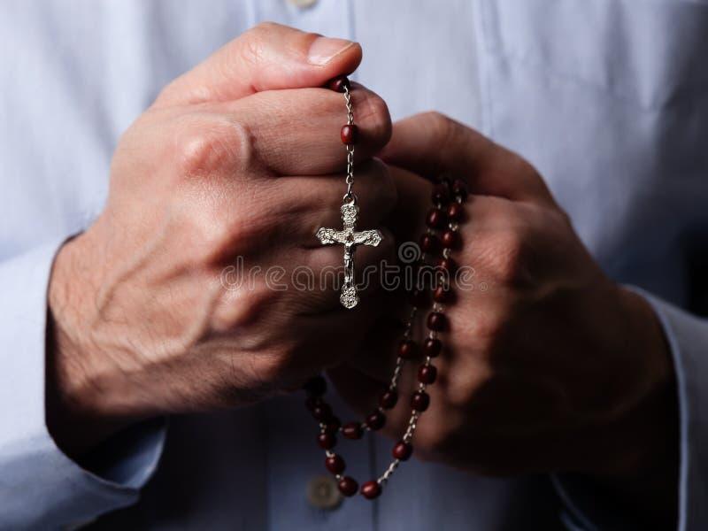 Mãos masculinas que rezam guardando um rosário com Jesus Christ na cruz ou no crucifixo no fundo preto imagem de stock royalty free