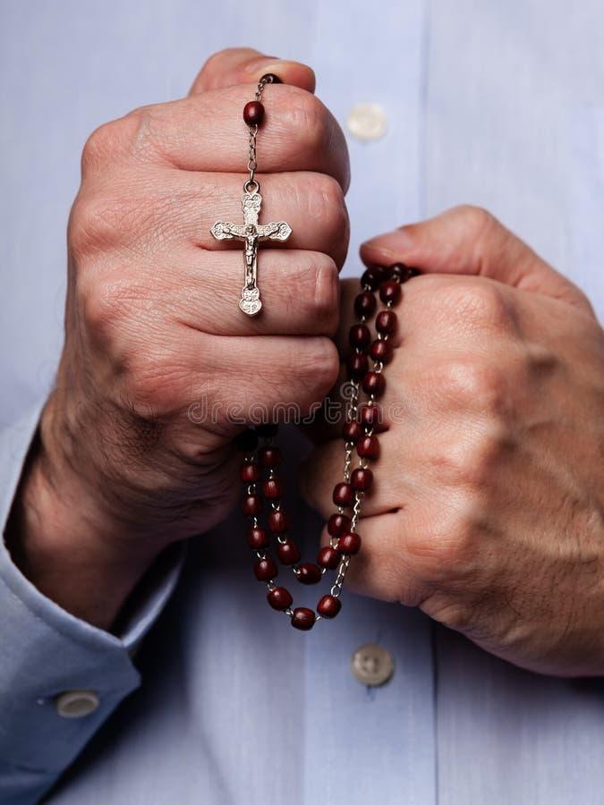 Mãos masculinas que rezam guardando um rosário com Jesus Christ na cruz ou no crucifixo no fundo preto fotos de stock royalty free