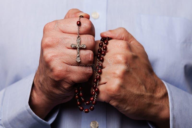 Mãos masculinas que rezam guardando um rosário dos grânulos com Jesus Christ na cruz ou no crucifixo foto de stock royalty free