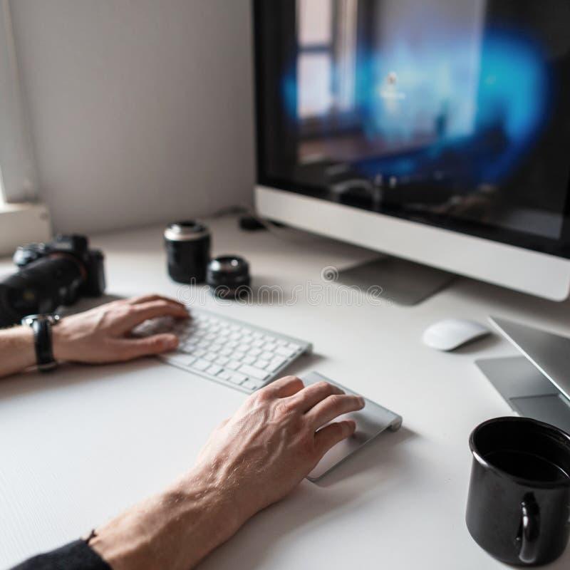 Mãos masculinas que trabalham no computador em um desktop branco com equipamento fotográfico e café Trabalhos do freelancer do fo imagens de stock royalty free