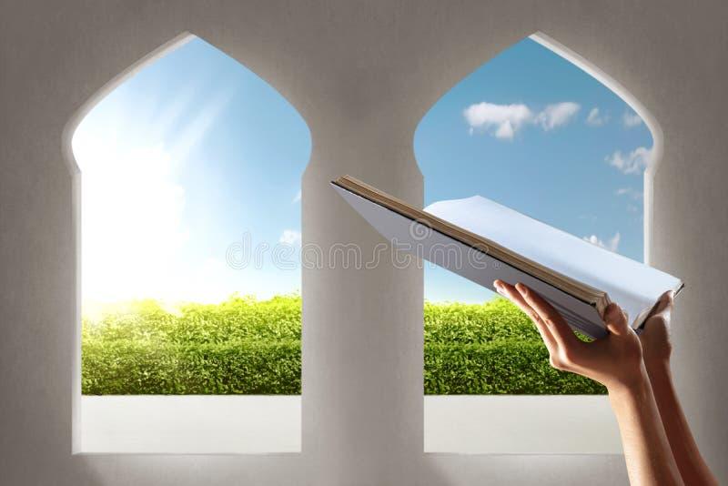 Mãos muçulmanas que mantêm o quran aberto na mesquita com opinião do jardim dos arcos da janela imagem de stock