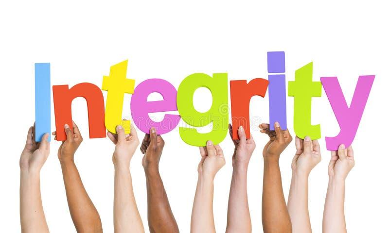Mãos Multi-étnicas que guardam a integridade da palavra imagens de stock royalty free