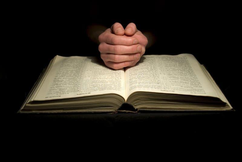 Mãos na Bíblia imagens de stock