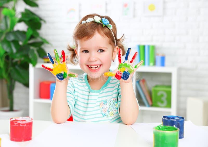 Mãos na menina feliz colorida da criança da pintura imagem de stock