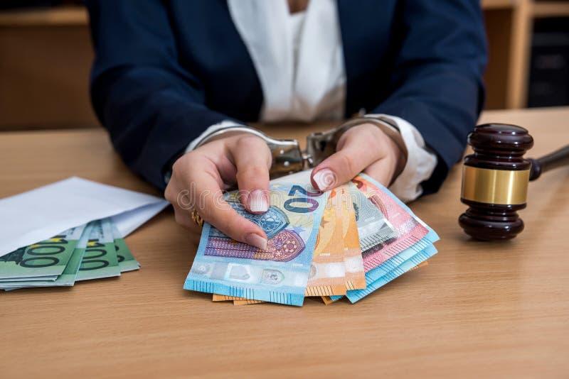 Mãos nas algemas prendidas para o subôrno com euro foto de stock royalty free