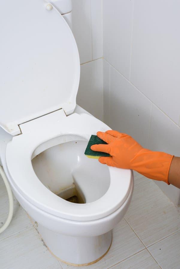 Mãos nas luvas alaranjadas que limpam WC, toalete, lavabos fotografia de stock