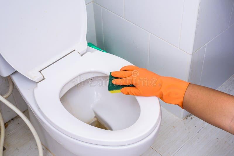 Mãos nas luvas alaranjadas que limpam WC, toalete, lavabos foto de stock