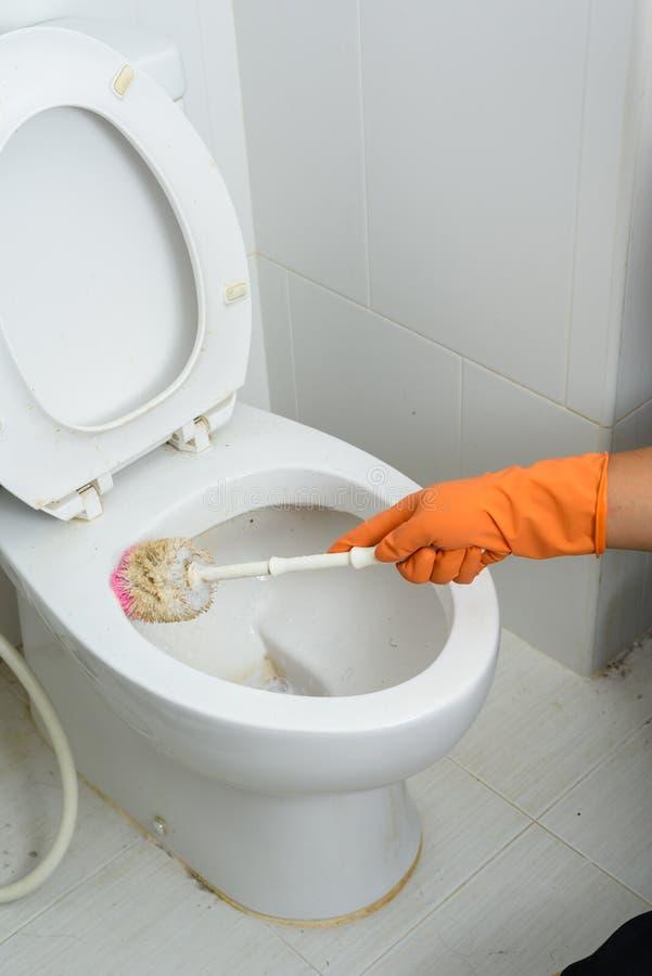 Mãos nas luvas alaranjadas que limpam WC, toalete, lavabos usando a escova foto de stock