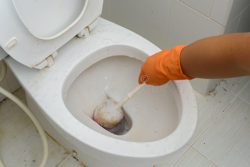 Mãos nas luvas alaranjadas que limpam WC, toalete, lavabos usando a escova imagens de stock