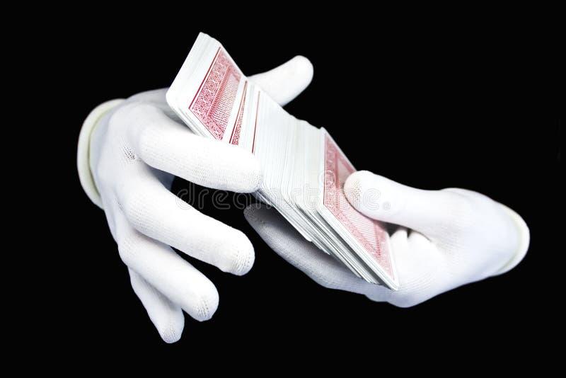 Mãos nas luvas brancas com um bloco de cartões de jogo foto de stock