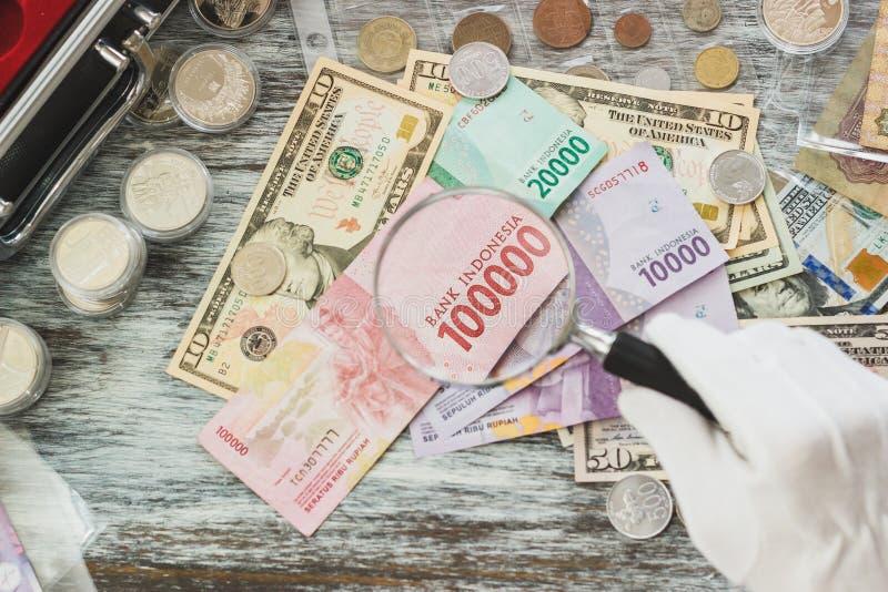 Mãos nas luvas brancas, em dólares americanos diferentes e em rupias indonésias, conceito da numismática fotos de stock