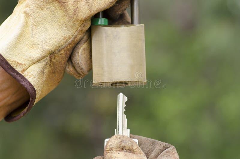 Mãos nas luvas com o cadeado chave e fechado fotografia de stock