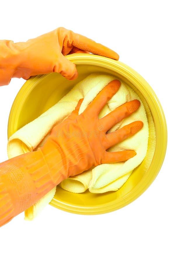 Mãos nas luvas de borracha que lavam a toalha de prato plástica fotografia de stock royalty free