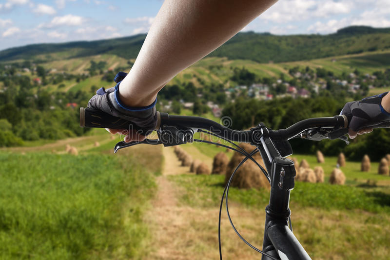 Mãos nas luvas que prendem o guiador de uma bicicleta Ciclista do Mountain bike que monta a única trilha Fazer ativo do atleta do fotografia de stock