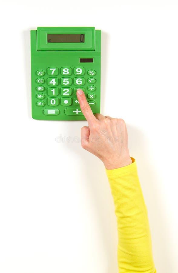 Mãos no revestimento amarelo e na calculadora verde fotos de stock royalty free