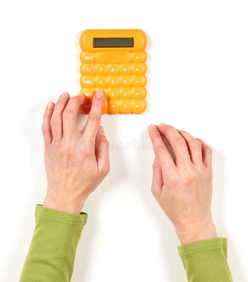 Mãos no revestimento verde e na calculadora amarela fotografia de stock royalty free