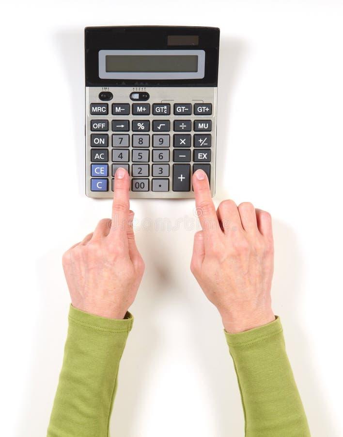 Mãos no revestimento verde e na calculadora cinzenta fotos de stock royalty free