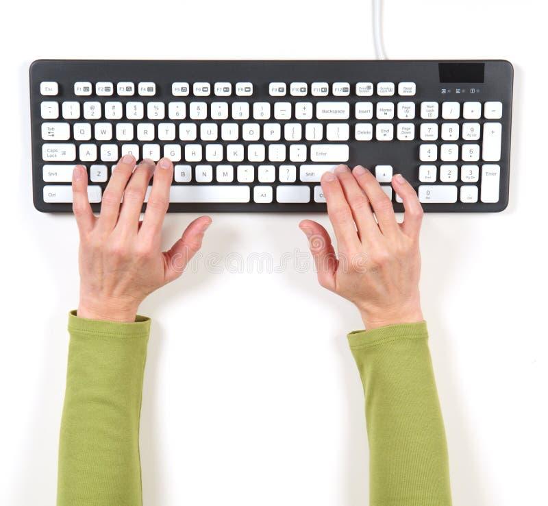 Mãos no revestimento verde e no teclado cinzento fotografia de stock royalty free