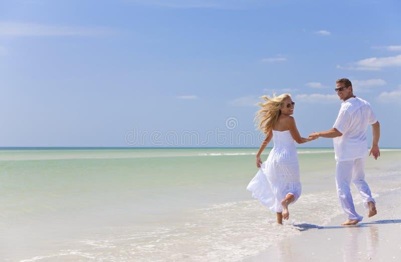 Mãos novas da terra arrendada dos pares em uma praia tropical fotos de stock royalty free
