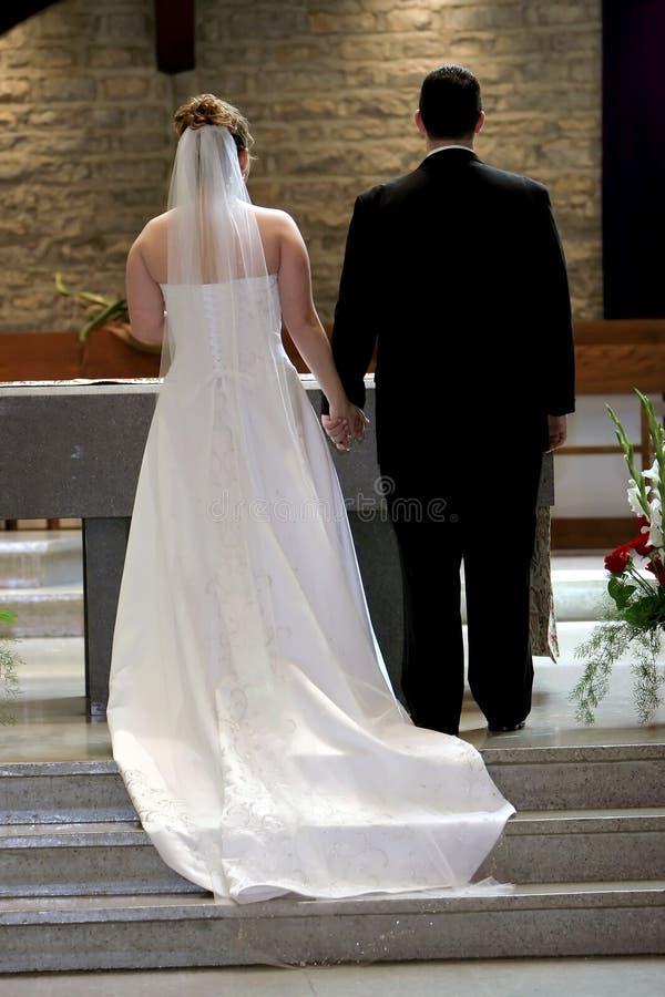 Mãos novas da terra arrendada dos pares no altar no dia do casamento fotos de stock royalty free